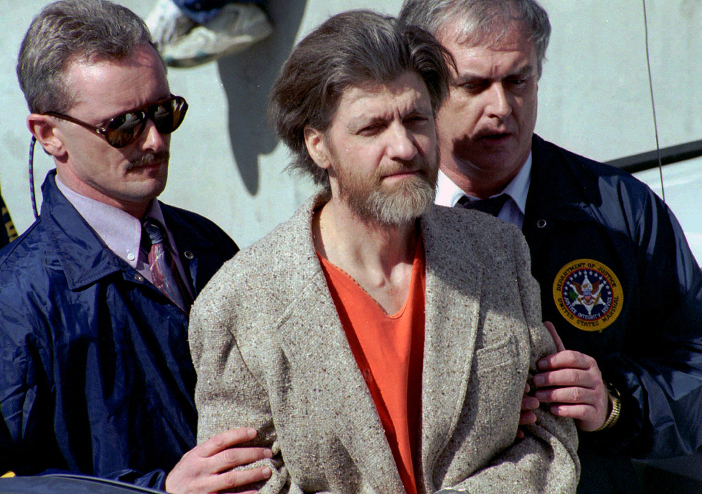 . FILE - In this April 4, 1996 file photo, Ted Kaczynski, better known as the Unabomber, is flanked by federal agents as he is led to a car from the federal courthouse in Helena, Mont. Kaczynski is serving a life sentence in a federal prison in Florence, Colorado, for a series of bombings, most through the mail, that killed three people and injured 23 others over 17 years. (AP Photo/John Youngbear, File)