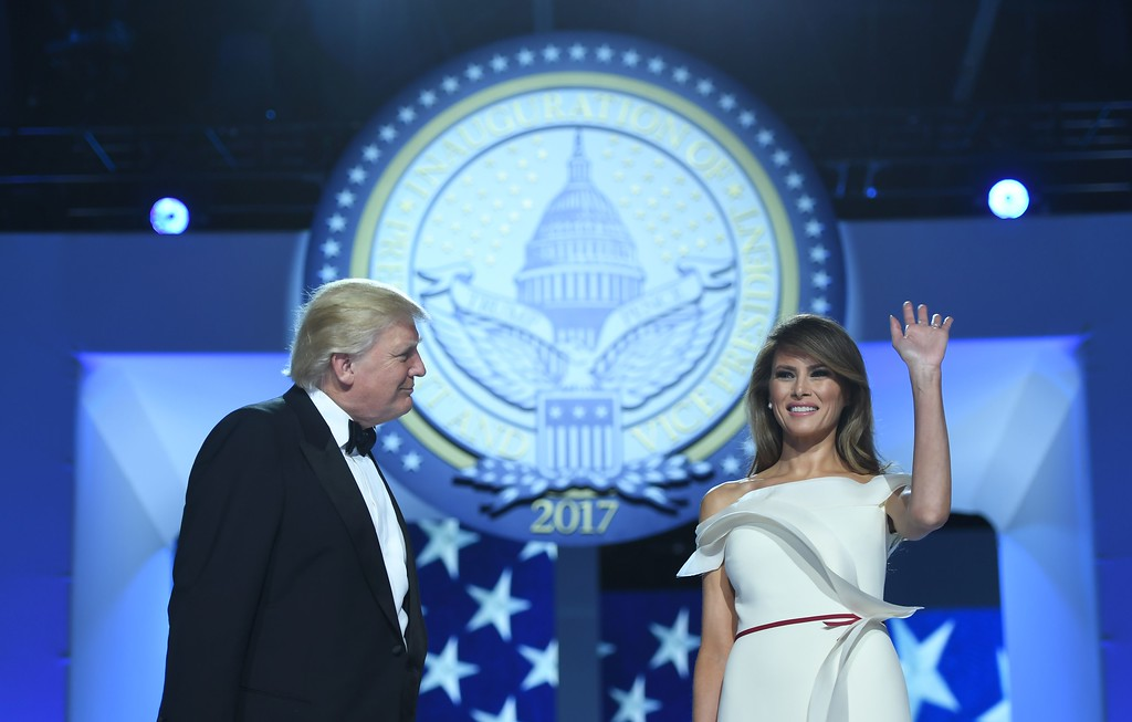 . US President Donald Trump looks on as first lady Melania Trump waves during the Freedom Ball at the Washington DC Convention Center following Donald Trump\'s inauguration as the 45th President of the United States, in Washington, DC, on January 20, 2017.  (JIM WATSON/AFP/Getty Images)