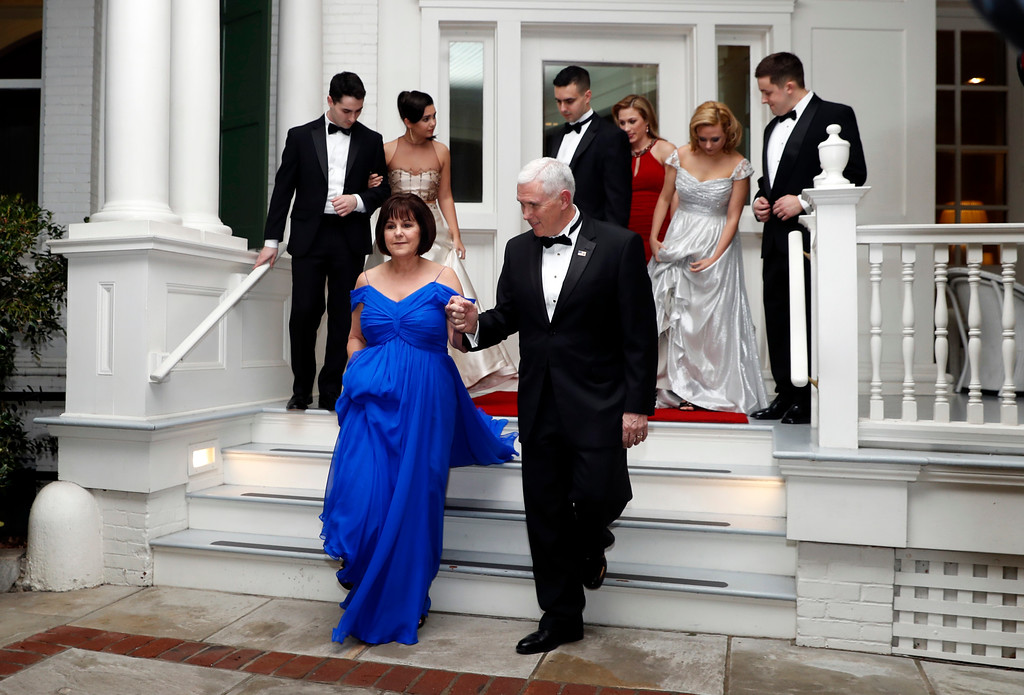 . Vice President Mike Pence right, assists his wife Karen Pence as they depart the Naval Observatory for several inaugural balls, Friday, Jan. 20, 2017 in Washington. (AP Photo/Alex Brandon)