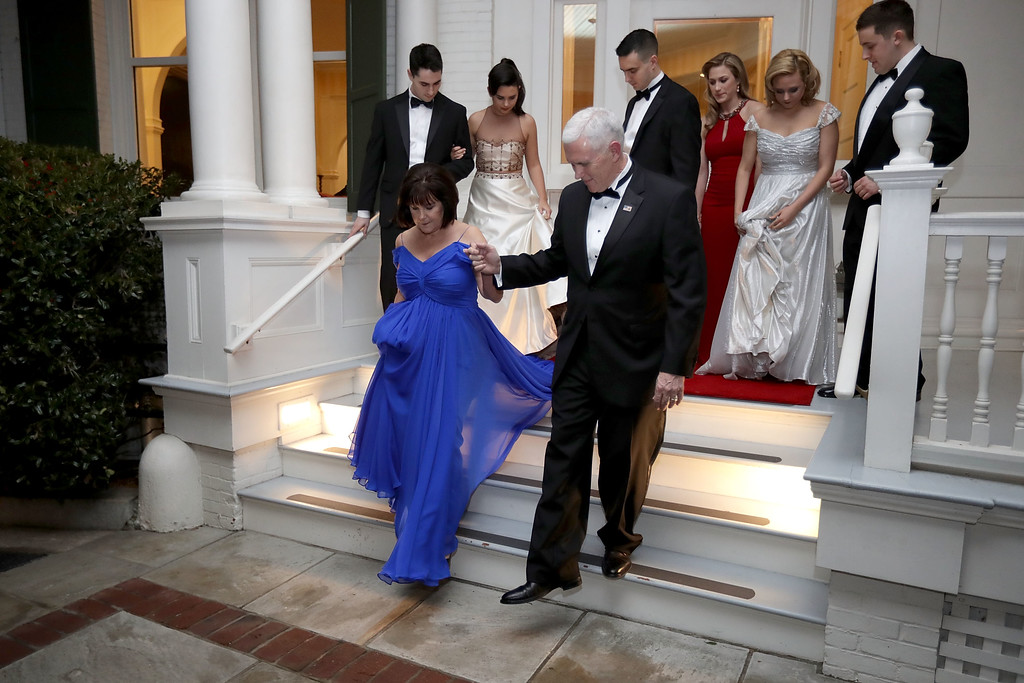 . WASHINGTON, DC - JANUARY 20:  U.S. Vice President Mike Pence (C) helps his wife Karen Pence down the steps of the front porch of the vice presidential residence at the U.S Naval Observatory before heading to the inaugural balls with their children January 20, 2017 in Washington, DC. The ball is part of the celebrations following the inauguration of Pence and U.S. President Donald J. Trump.  (Photo by Chip Somodevilla/Getty Images)