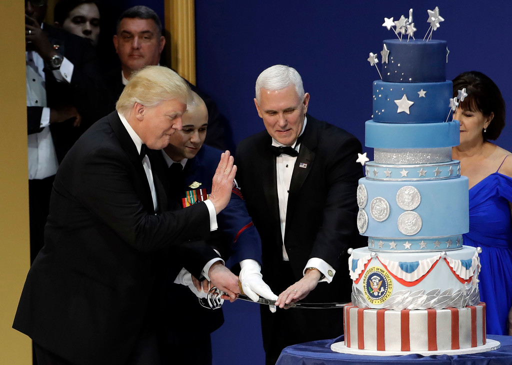 . President Donald J. Trump, left, and Vice President Mike Pence, right, are helped by Coast Guard Petty Officer 2nd Class Matthew Babot, center, as they cut a cake at The Salute To Our Armed Services Inaugural Ball Friday, Jan. 20, 2017, in Washington. (AP Photo/David J. Phillip)