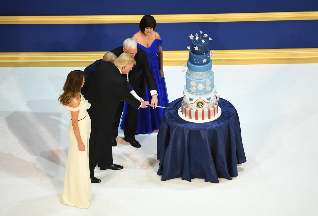 . US President Donald Trump, the first lady Melania Trump, US Vice President Mike Pence, and his wife Karen cut a cake after dancing at the Armed Services ball at the National Building museum following Donald Trump\'s inauguration as the 45th President of the United States, in Washington, DC, on January 20, 2017.  (JIM WATSON/AFP/Getty Images)