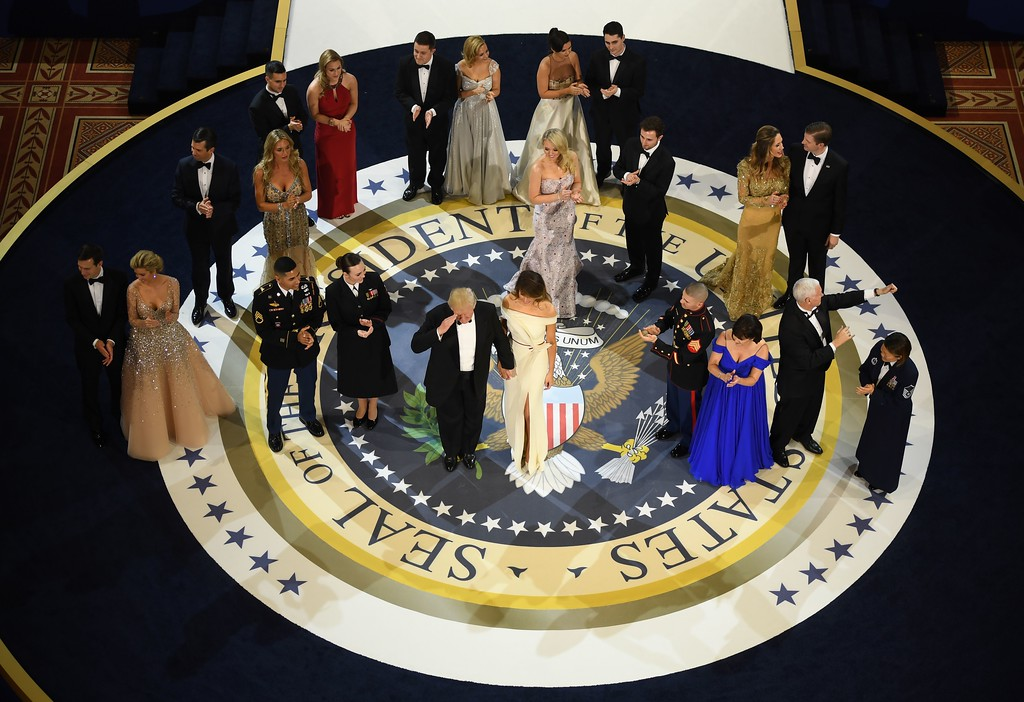 . US President Donald Trump, the first lady Melania Trump, US Vice President Mike Pence, and his wife Karen look on with members of the military and their families after dancing at the Armed Services ball at the National Building museum following Donald Trump\'s inauguration as the 45th President of the United States, in Washington, DC, on January 20, 2017.  (JIM WATSON/AFP/Getty Images)