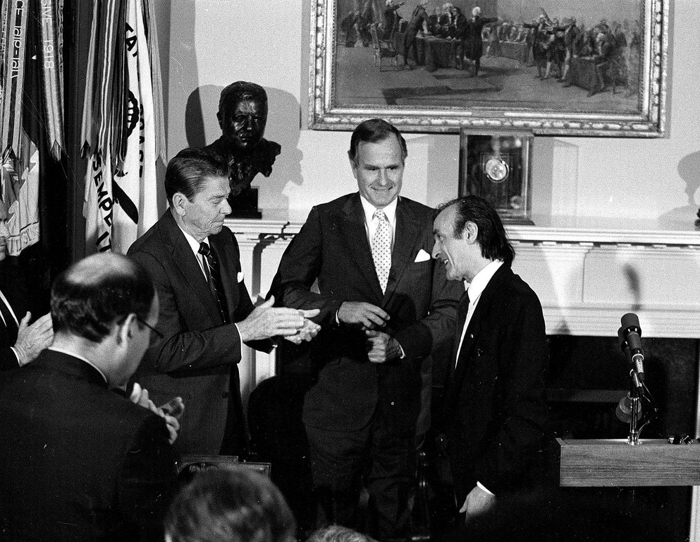 """. U.S. President Ronald Reagan, left, applaudes along with Vice President George Bush, center, after Elie Wiesel, Chairman of  \""""The President\'s Commission on the Holocaust,\"""" gave his speech at the White House in Washington, D.C., on April 19, 1985.  (AP Photo/Charles Tasnadi)"""