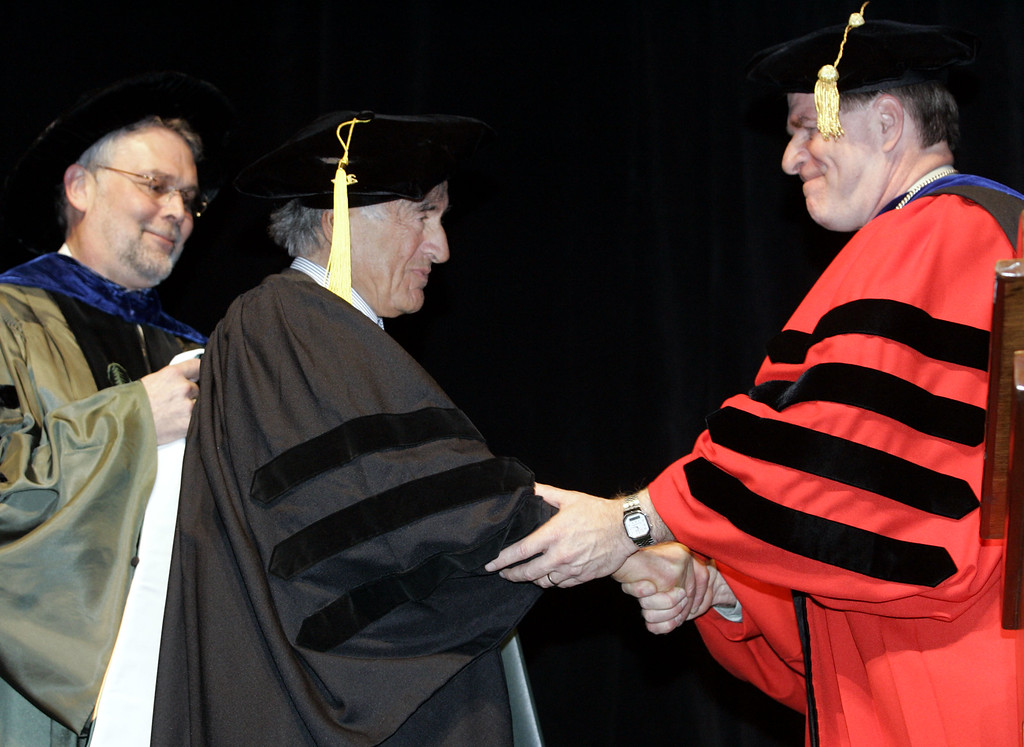 """. Nobel Peace Prize winner Elie Wiesel, center, the Holocaust survivor who recounted his experiences in the award-winning memoir \""""Night,\"""" shakes hands with University of Vermont President Daniel Mark Fogel, right, after receiving an honorary degree as UVM Provost John Hughes, left, looks on during ceremonies at the University of Vermont, in Burlington, Vt., Wednesday, April 25, 2007. (AP Photo/Alden Pellett)"""