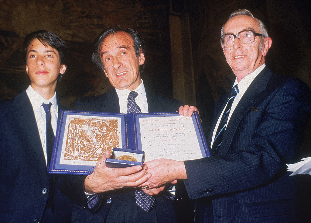 """. American author Elie Wiesel, center, with his son, Elisha, left, and Egil Aarvik, Chairman of the Nobel committee, pose with the Nobel prize in hand in Oslo, Norway on Dec. 10, 1986.  Wiesel is the Chairman of  \""""The President\'s Commission on the Holocaust.\""""  (AP Photo/Inge Gjellesvik)"""