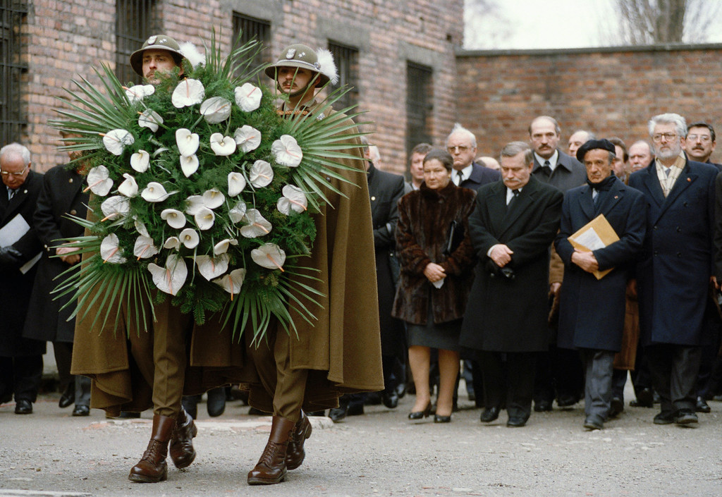 . Polish soldiers carry a wreath to the Wall of Death at the former Nazi concentration camp in Auschwitz, Poland, during the official ceremony of the 50th anniversary of the camp\'s liberation, Jan. 27, 1993. First row in the background shows from left, French Minister of Social Affairs Simone Veil, Polish President Lech Walesa, Nobel Peace Prize winner Elie Wiesel. (AP Photo/Czarek Solokowski)