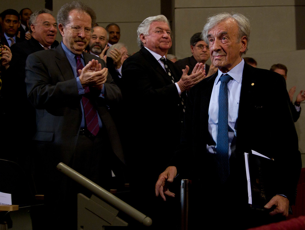 . Nobel Peace Prize laureate and Holocaust survivor Elie Wiesel, right,  walks to his seat after introducing President Barack Obama, not seen, at the Holocaust Memorial Museum, Monday, April 23, 2012, in Washington. (AP Photo/Carolyn Kaster)