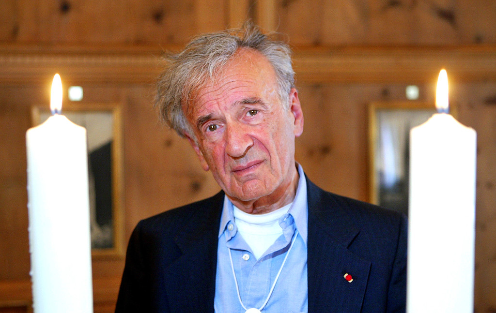 . Holocaust survivor and Nobel peace prize winner Elie Wiesel stands between two candles during a \'Holocaust Commemoration Ceremony\' at the World Economic Forum in Davos, Switzerland, Wednesday Jan. 26, 2005.  (AP Photo/Michael Probst)