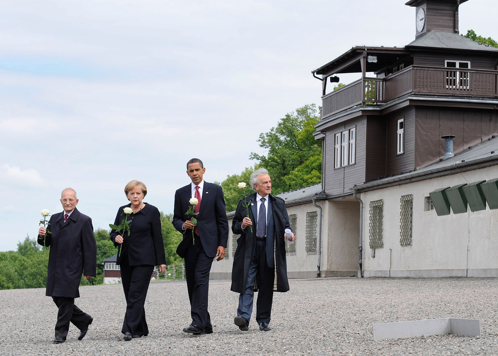 . US President Barack Obama, 2nd right, German chancellor Angela Merkel, 2nd left, and Buchenwald survivors Elie Wiesel, right, and Bertrand Herz, left, walk away from the gate building with roses in their hands at the Buchenwald concentration camp near Weimar, Germany, Friday, June 5, 2009.  (AP Photo/Oliver Multhaup, POOL)
