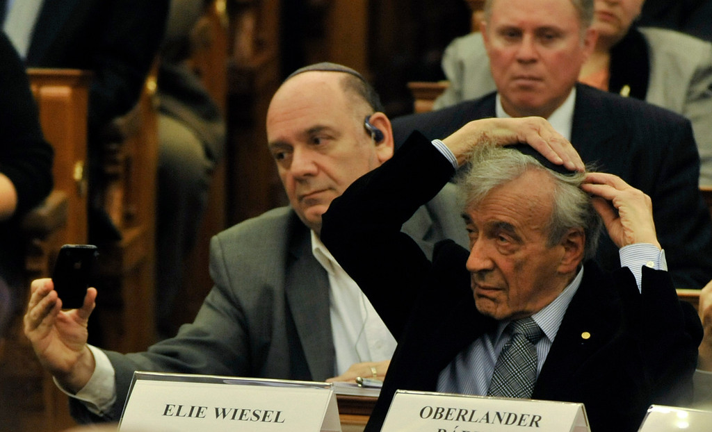 """. A man takes a picture of Elie Wiesel, right, 81 year old Holocaust survivor and Nobel Peace Prize winning author, while he puts on his kippah  in the Hungarian Parliament building in Budapest, Hungary, Wednesday, Dec. 9, 2009. Wiesel arrived to Hungary Wednesday on his first official visit since the Holocaust on the occasion of the 20th birthday of the Chabad Lubavitch movement and to participate in the \""""Jewish Hungarian Solidarity\' symposium. (AP Photo/Bela Szandelszky)"""