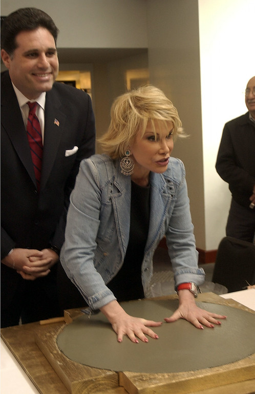 . Tony-nominated actress and fashion maven, Joan Rivers, center, flanked by Miami Beach Mayor, David Dermer, left, places her hands on cement at the Jackie Gleason Theater in Miami Beach, Fla., Thursday, March 25, 2004, where she was inducted into the Gleason\'s Walk of Stars and given a key to the city.(AP Photo/Yesikka Vivancos)