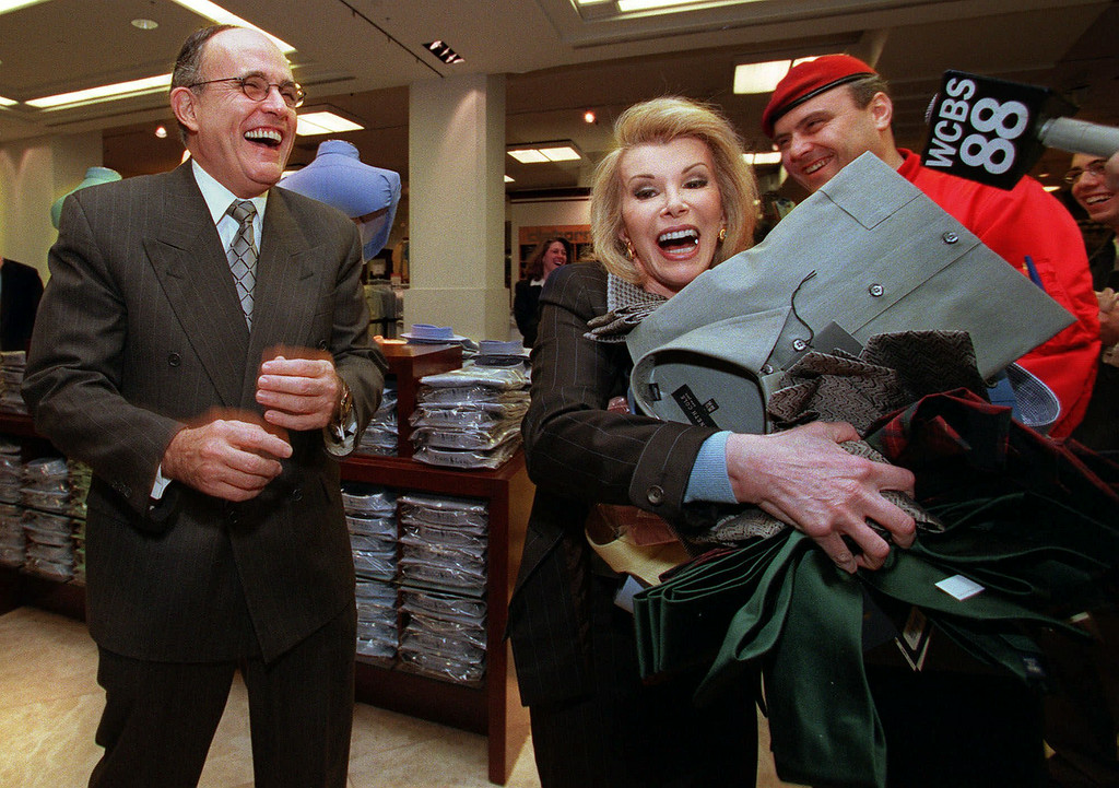 ". New York City Mayor Rudolph Giuliani, left, laughs as entertainer Joan Rivers carries a pile of clothing to a cash register at Macy\'s to kick off the start of ""no sales tax\"" Wednesday, March 1, 2000, in New York City. The New York state 4 percent sales tax on clothes and footwear will be eliminated on purchases of less than $110, but only two cities, New York and Sherill in Oneida County, and 14 of the state\'s 62 counties are dropping their local sales tax. WABC radio host Curtis Sliwa is at right.  (APPhoto/Diane Bondareff)"