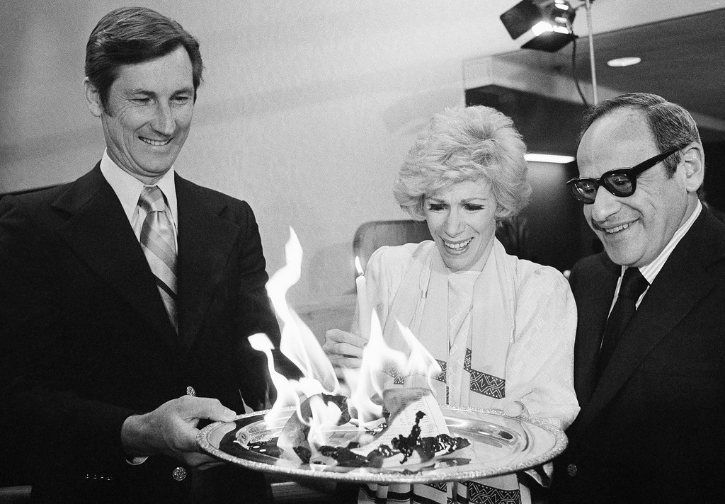 ". Director-comedienne Joan Rivers watches the loan papers she signed, putting her home up as collateral for money to finish a picture she directed, go up in flames in Beverly Hills, Calif., May 24, 1978. The picture, ""Rabbit Test,\"" has grossed $10 million thus far. The \""burning\"" ceremony took place at a bank in Beverly Hills from which she secured the loan. Former Yankees catcher is see right; man at left is unidentified. (AP Photo/Lennox McLendon)"