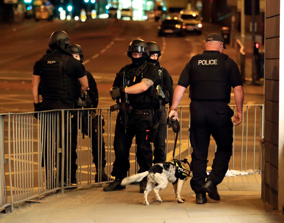 . Armed police work after an explosion at the Manchester Arena in Manchester, England Tuesday, May 23, 2017. An explosion struck an Ariana Grande concert attended by thousands of young music fans in northern England late Monday, killing over a dozen people and injuring dozens in what police said Tuesday was being treated as a terrorist attack. (Peter Byrne/PA via AP)