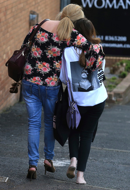. A fan is comforted as she leaves the Park Inn hotel in central Manchester, England Tuesday May 23 2017. Over a dozen people were killed in an explosion following a Ariana Grande concert at the Manchester Arena late Monday evening. (AP Photo/Rui Vieira)