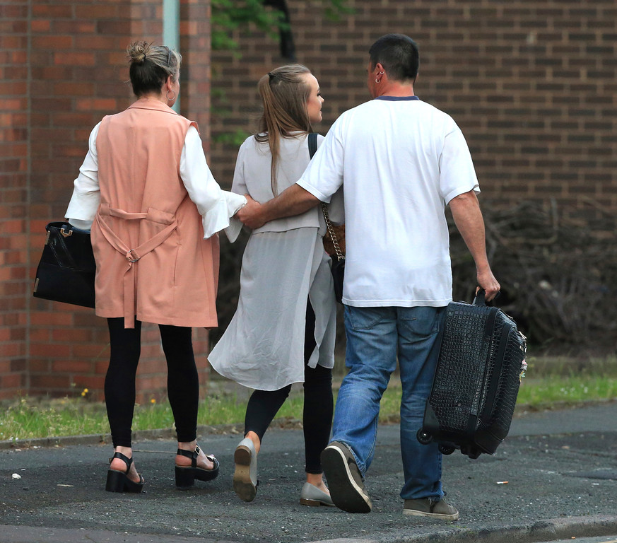 . A fan leaves with parents at the Park Inn hotel in central Manchester, England Tuesday May 23 2017.  An apparent suicide bomber set off an improvised explosive device that killed over a dozen people at the end of an Ariana Grande concert on Monday, Manchester police said Tuesday.  (AP Photo/Rui Vieira)