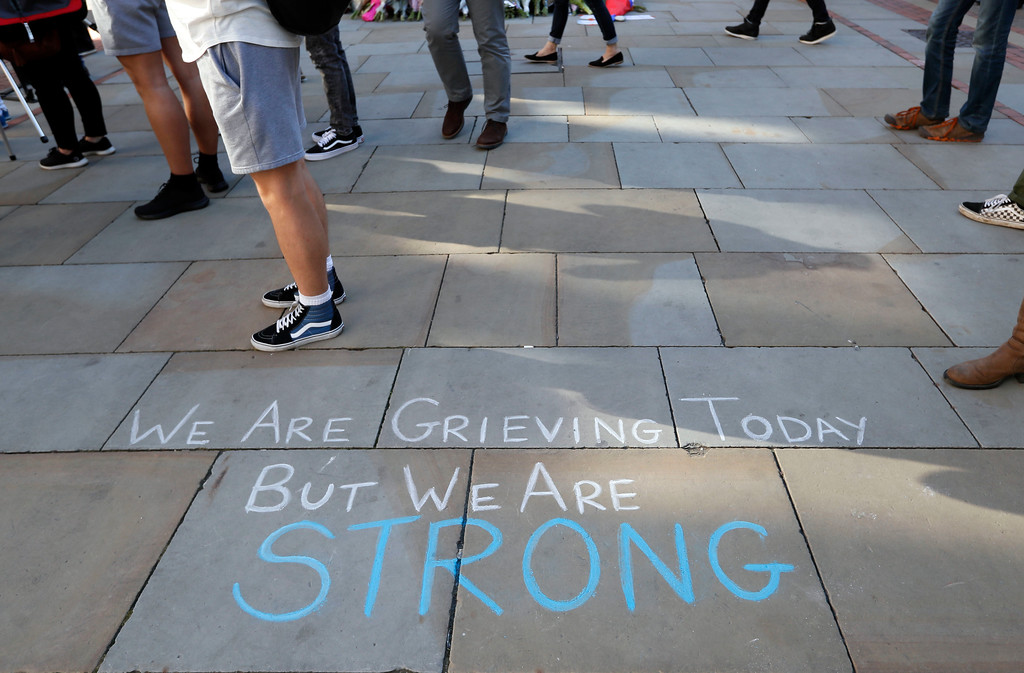. A message is written on the pavement in Manchester, England, Tuesday May 23, 2017, the day after the suicide attack at an Ariana Grande concert that left 22 people dead as it ended on Monday night. (AP Photo/Kirsty Wigglesworth)