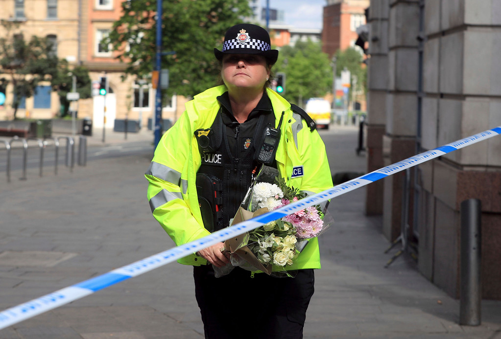. A police officer carries a floral tribute close to the Manchester Arena, the morning after a suicide bomber killed more than a dozen people as an explosion tore through fans leaving a pop concert in Manchester England Tuesday May 23, 2017. (Danny Lawson/PA  via AP)
