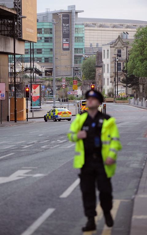 . Police block a road near to the Manchester Arena, seen at the right, in central Manchester, England Tuesday May 23 2017.  An explosion struck an Ariana Grande concert attended by thousands of young music fans in northern England, killing people and injuring dozens in what police said Tuesday was being treated as a terrorist attack. (AP Photo/Rui Vieira)
