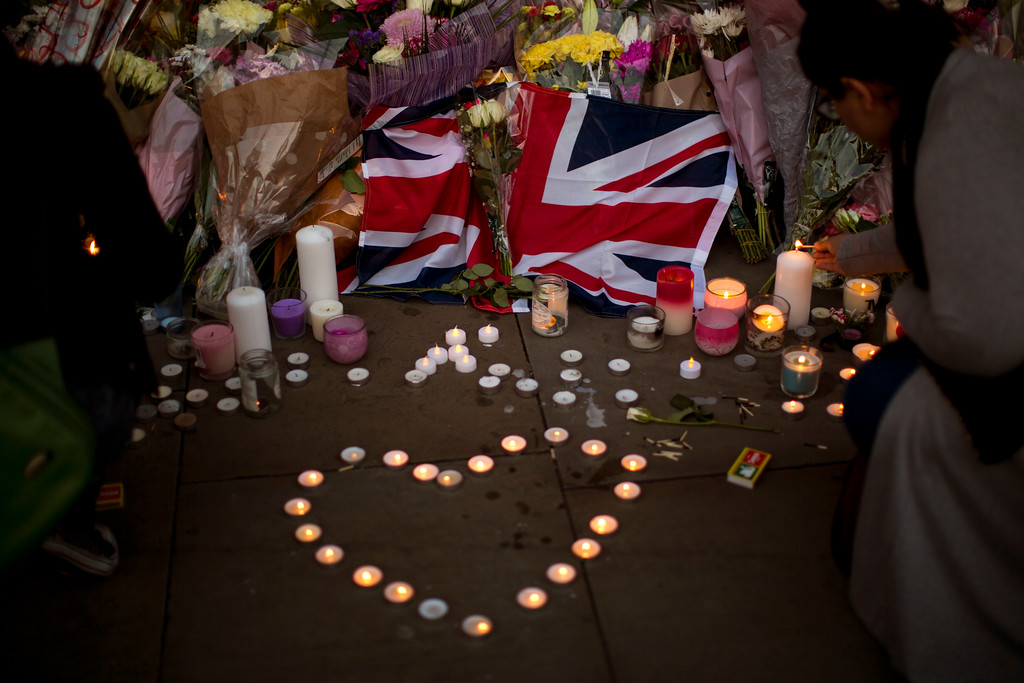 . A British flag is seen next to flowers after a vigil in Albert Square, Manchester, England, Tuesday May 23, 2017, the day after the suicide attack at an Ariana Grande concert that left 22 people dead as it ended on Monday night. (AP Photo/Emilio Morenatti)