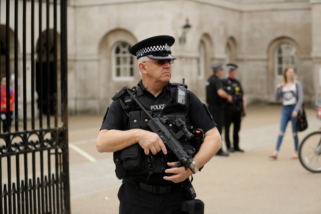 . An armed British police officer stands guard outside Horse Guards, on Whitehall in London, Tuesday May 23, 2017. The day after an apparent suicide bomber attacked an Ariana Grande concert as it ended Monday night, killing over a dozen of people among a panicked crowd of young concertgoers. (AP Photo/Matt Dunham)