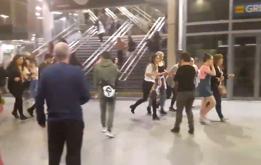 . This image shows  people running through Manchester Victoria station after an explosion at Manchester Arena. in Manchester England, Monday May 22, 2017. An apparent suicide bomber set off an improvised explosive device that killed over a dozen people at the end of an Ariana Grande concert on Monday, Manchester police said Tuesday May 23, 2017.  The station is very near the arena. (Zach Bruce/PA via AP)