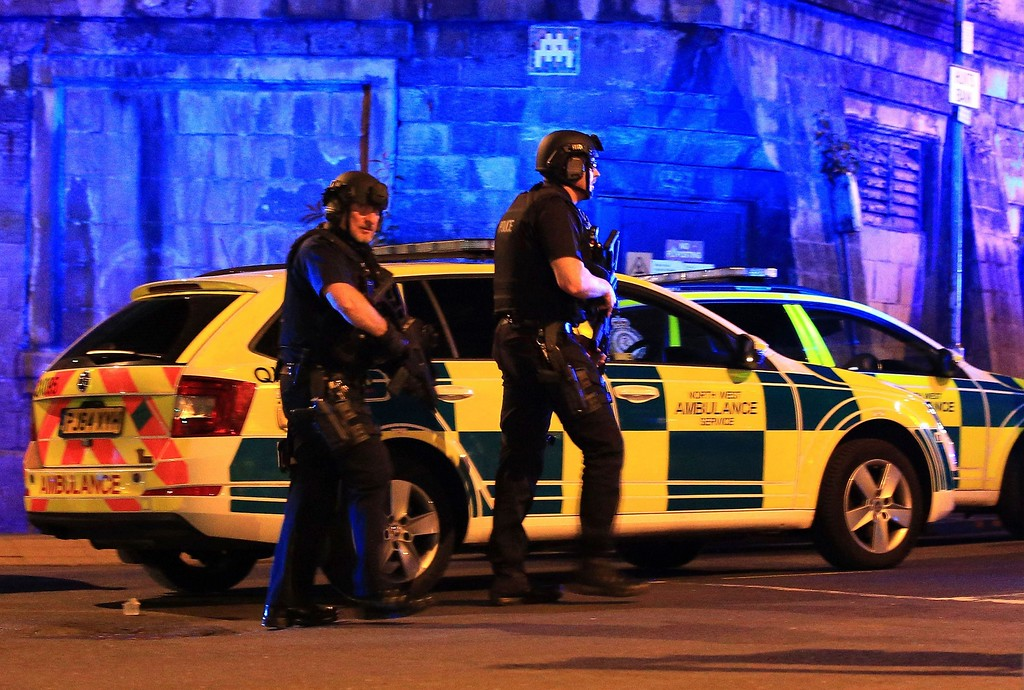 . Armed police work at Manchester Arena after reports of an explosion at the venue during an Ariana Grande gig in Manchester, England Monday, May 22, 2017. Several people have died following reports of an explosion Monday night at an Ariana Grande concert in northern England, police said. A representative said the singer was not injured. (Peter Byrne/PA via AP)