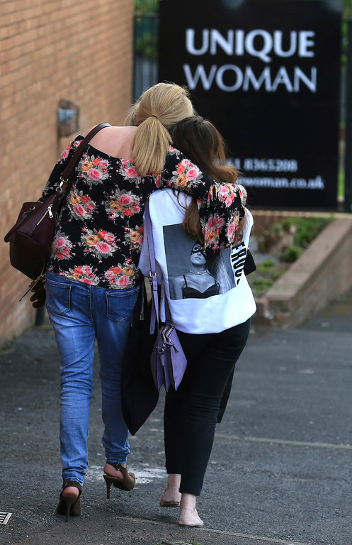 . A fan is comforted as she leaves the Park Inn hotel in central Manchester, England, Tuesday May 23, 2017, the day after an apparent suicide bomber attacked an Ariana Grande concert as it ended Monday night, killing over a dozen of people among a panicked crowd of young concertgoers. (AP Photo/Rui Vieira)