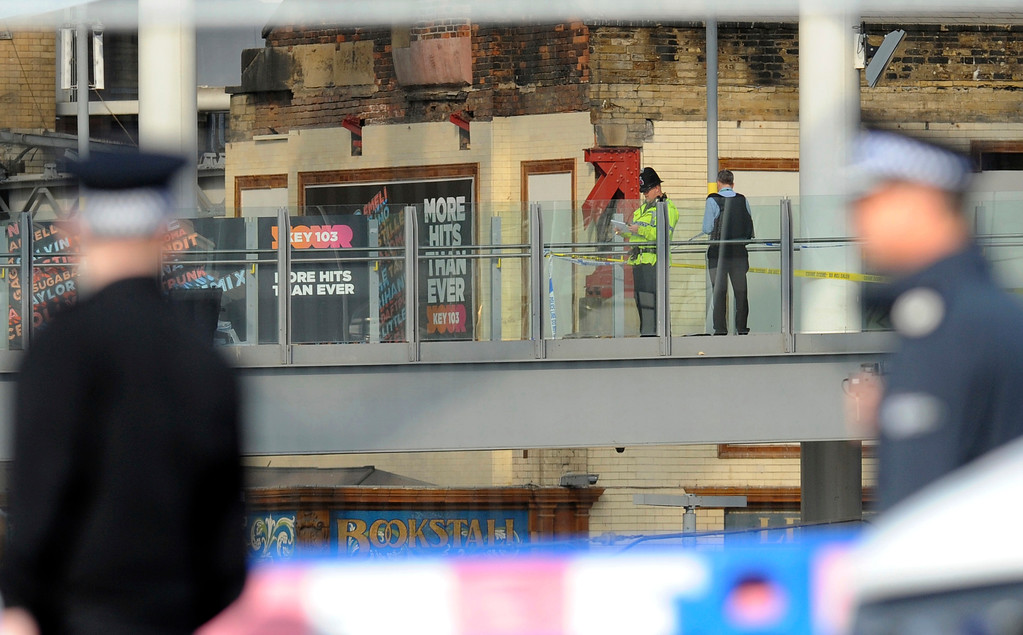 . Police investigate on a bridge which links Victoria railway station to the Manchester Arena in central Manchester, England, Tuesday, May 23 2017. An apparent suicide bomber set off an improvised explosive device that killed over a dozen people at the end of an Ariana Grande concert on Monday, Manchester police said Tuesday. (AP Photo/Rui Vieira)
