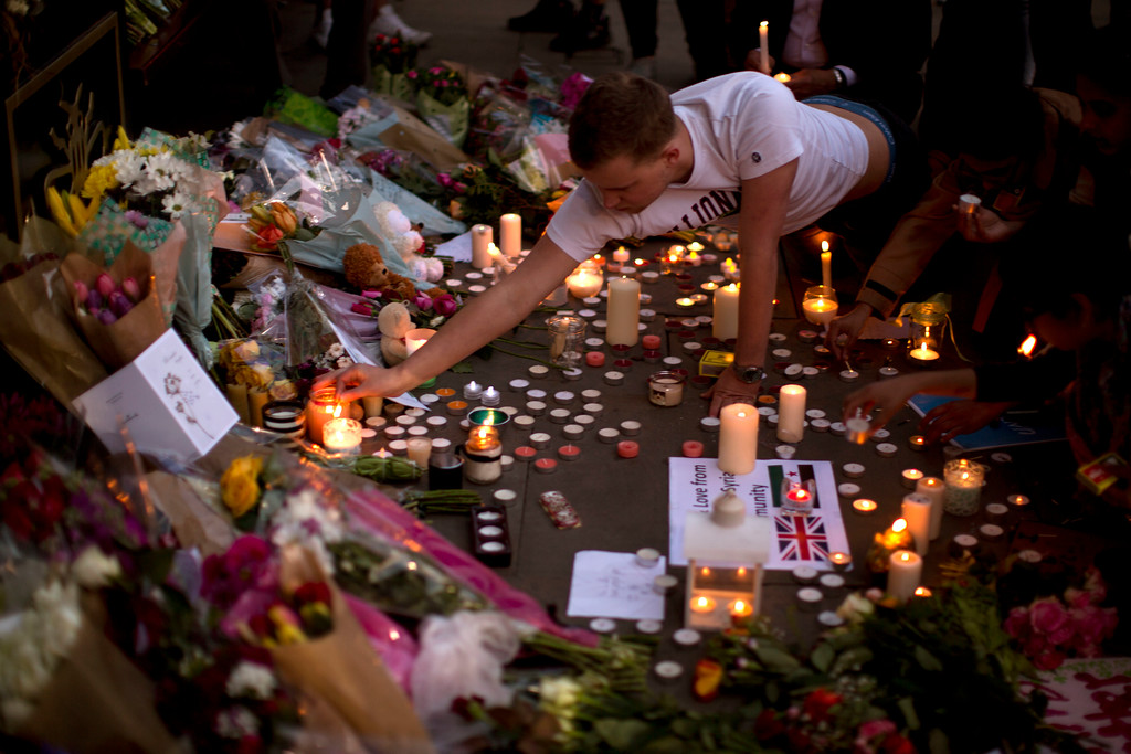 . A man lights candles after a vigil in Albert Square, Manchester, England, Tuesday May 23, 2017, the day after the suicide attack at an Ariana Grande concert that left 22 people dead as it ended on Monday night. (AP Photo/Emilio Morenatti)