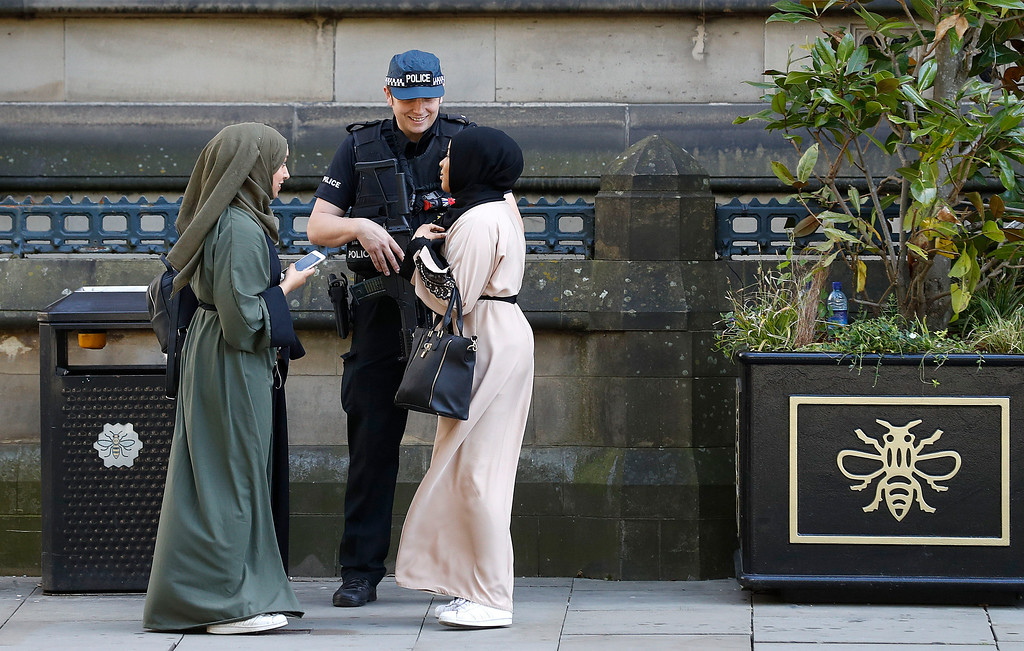 . An armed police stand guard  speaks with two young women at Albert Square, Manchester, England Tuesday May 23, 2017,  where later they will hold a vigil to the victims of the explosion on Monday evening.  A suicide bomber killed more than a dozen people, including children, as an explosion tore through fans leaving a pop concert in Manchester.  (Martin Rickett/PA via AP)