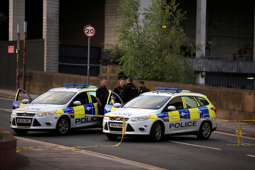 . Police officers stand next to their vehicles near the Manchester Arena after a blast at Ariana Grande concert Tuesday May 23, 2017. An explosion struck the concert attended by thousands of young music fans in northern England, killing more than a dozen of people and injuring dozens in what police said Tuesday was being treated as a terrorist attack.  (Peter Byrne/PA via AP)