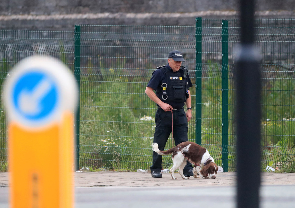 . A police officer with a sniffer dog patrols near the Manchester Arena in Manchester, England Tuesday, May 23, 2017. An explosion struck an Ariana Grande concert attended by thousands of young music fans in northern England late Monday, killing over a dozen people and injuring dozens in what police said Tuesday was being treated as a terrorist attack. (Danny Lawson/PA via AP)