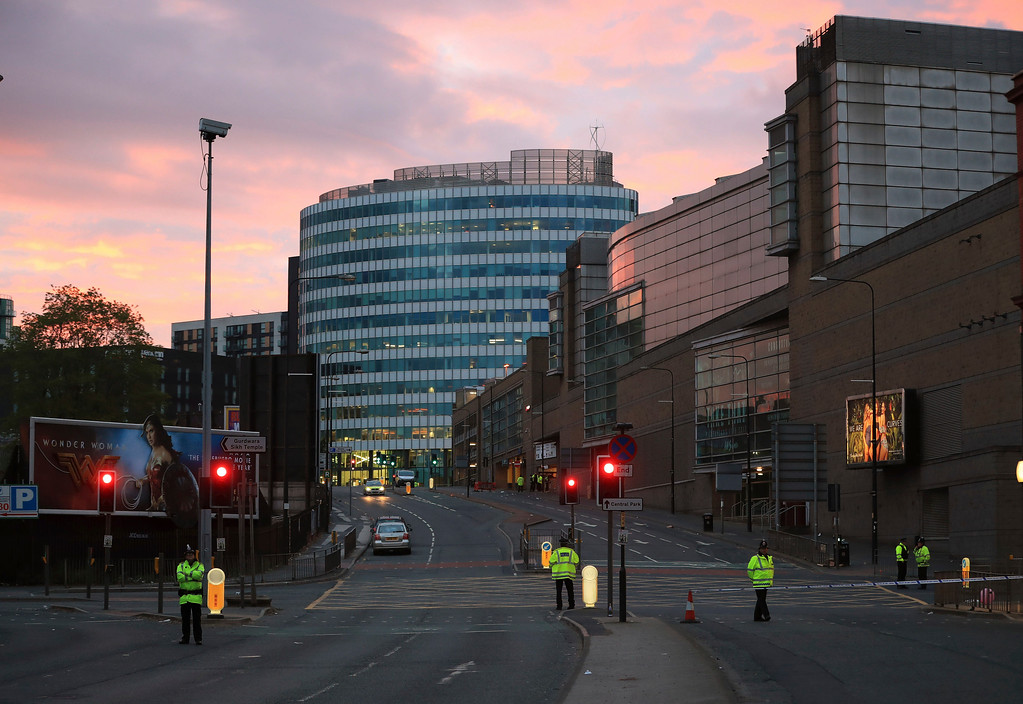 . Police stand guard at dawn, after a blast at the Manchester Arena Tuesday, May 23, 2017. An explosion struck an Ariana Grande concert attended by thousands of young fans in northern England Monday night, killing more than a dozen of people and injuring dozens in what police were treating as a terrorist attack. (Peter Byrne/PA via AP)