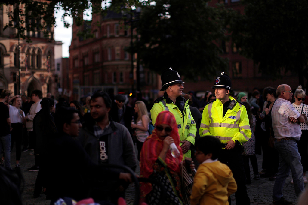 . Police patrol as people attend a vigil in Albert Square, Manchester, England, Tuesday May 23, 2017, the day after the suicide attack at an Ariana Grande concert that left 22 people dead as it ended on Monday night. (AP Photo/Emilio Morenatti)