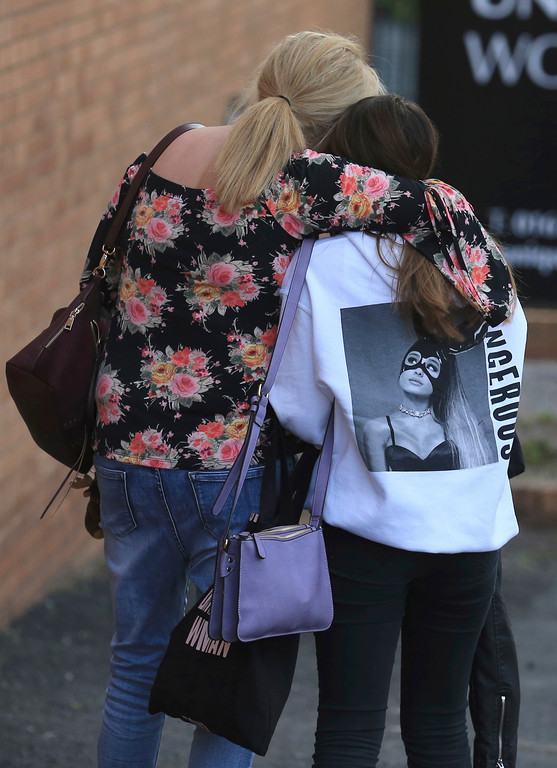 . A fan is comforted as she leaves the Park Inn hotel in central Manchester, England Tuesday May 23 2017. Over a dozen of people were killed in an explosion following a Ariana Grande concert at the Manchester Arena late Monday evening. (AP Photo/Rui Vieira)