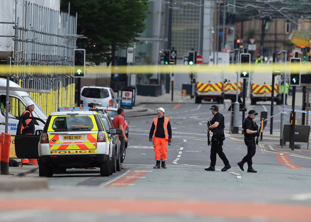 . Police guard close to the Manchester Arena in Manchester, Britain, Tuesday May 23, 2017, a day after an explosion. An apparent suicide bomber set off an improvised explosive device that killed over a dozen people at the end of an Ariana Grande concert, Manchester police said Tuesday. (Peter Byrne/PA via AP)