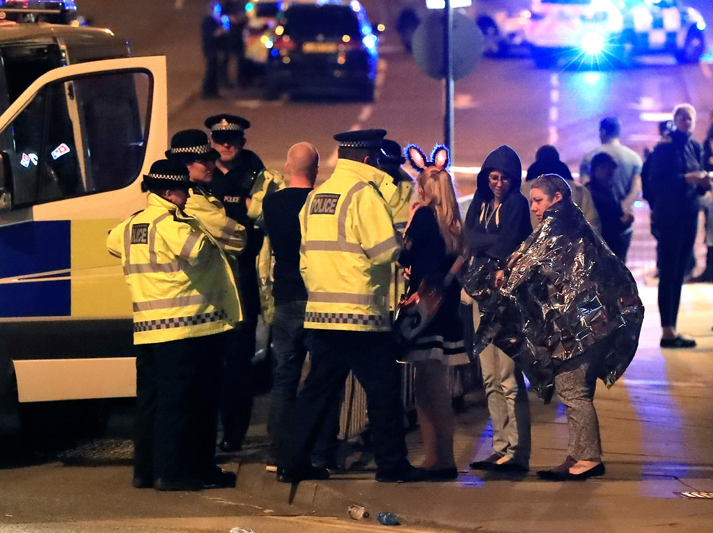 . Emergency services personnel speak to people outside Manchester Arena after reports of an explosion at the venue during an Ariana Grande concert in Manchester, England, Monday, May 22, 2017. Several people have died following an explosion Monday night at an Ariana Grande concert in northern England, police and witnesses said. The singer was not injured, according to a representative. (Peter Byrne/PA via AP)