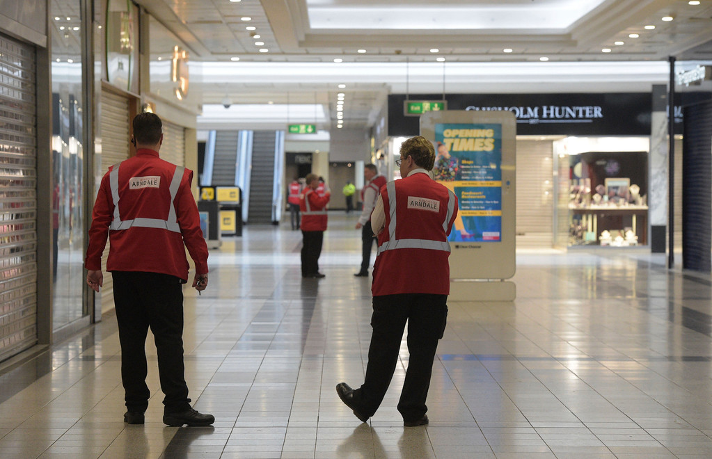. Security staff inside the Arndale Shopping Centre in central Manchester which was evacuated while an incident was dealt with by police Tuesday May 23, 2017.  Security was heightened in the city after an explosion at pop concert in the city on Monday.  (Ben Birchall/PA via AP)