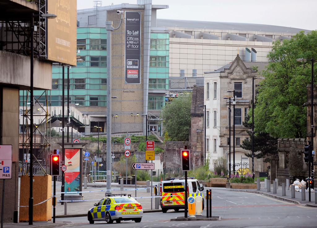 . Police block roads near to the Manchester Arena, seen at the right, in central Manchester, England Tuesday May 23, 2017.  An explosion struck an Ariana Grande concert attended by thousands of young music fans in northern England, killing people and injuring dozens in what police said Tuesday was being treated as a terrorist attack. (AP Photo/Rui Vieira)