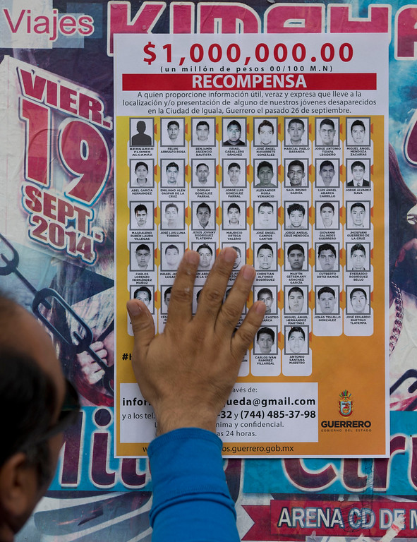 . FILE - In this Oct. 16, 2014 file photo, a man places a missing persons\' poster offering 1,000,000.00 Mexican pesos or about 74,000.00 U.S. dollars, leading to information on the 43 college students who went missing, in Chilpancingo, Mexico. Over time, 10,000 federal agents and dozens of forensics investigators in hazmat suits joined the search, and a reward was offered for information on the missing students. (AP Photo/Eduardo Verdugo, File)