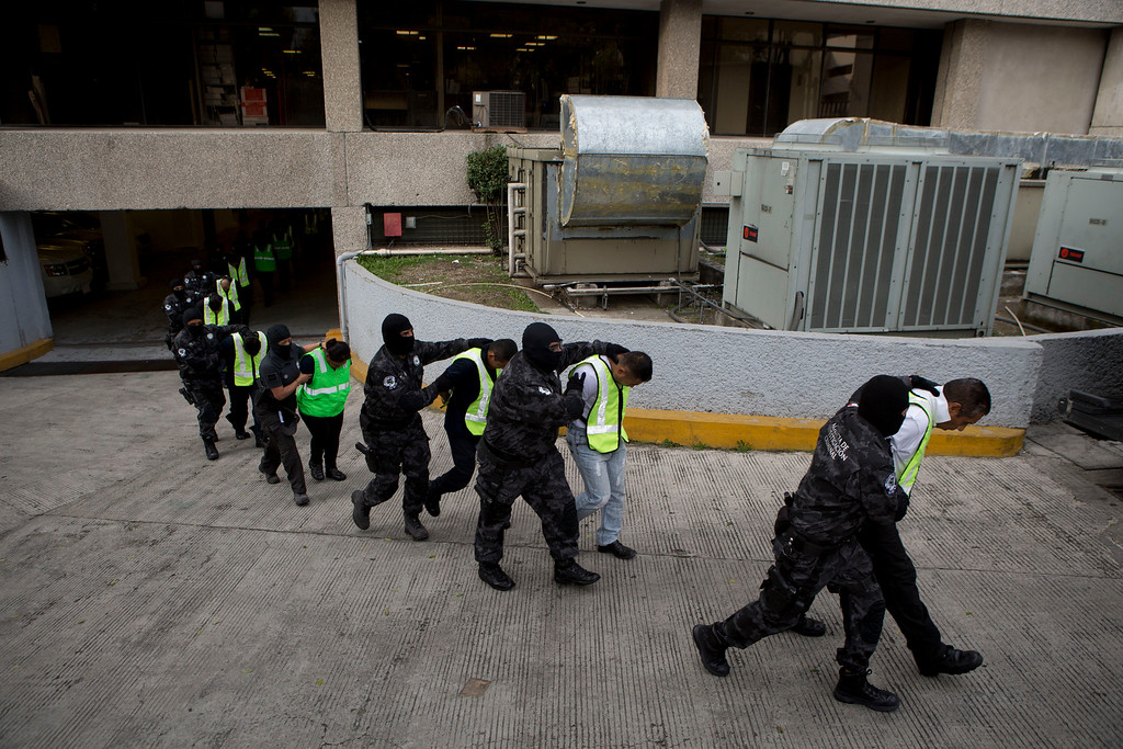 . FILE - In this Oct. 17, 2014 file photo, municipal police officers who are suspected of being involved in the disappearance of 43 students are marched to waiting transport at the Mexican attorney generals\' organized crime unit headquarters in Mexico City. The government says it still does not know what happened to the young people after they were rounded up by local police in Iguala and allegedly handed over to gunmen from a drug cartel Sept. 26. (AP Photo/Rebecca Blackwell, File)