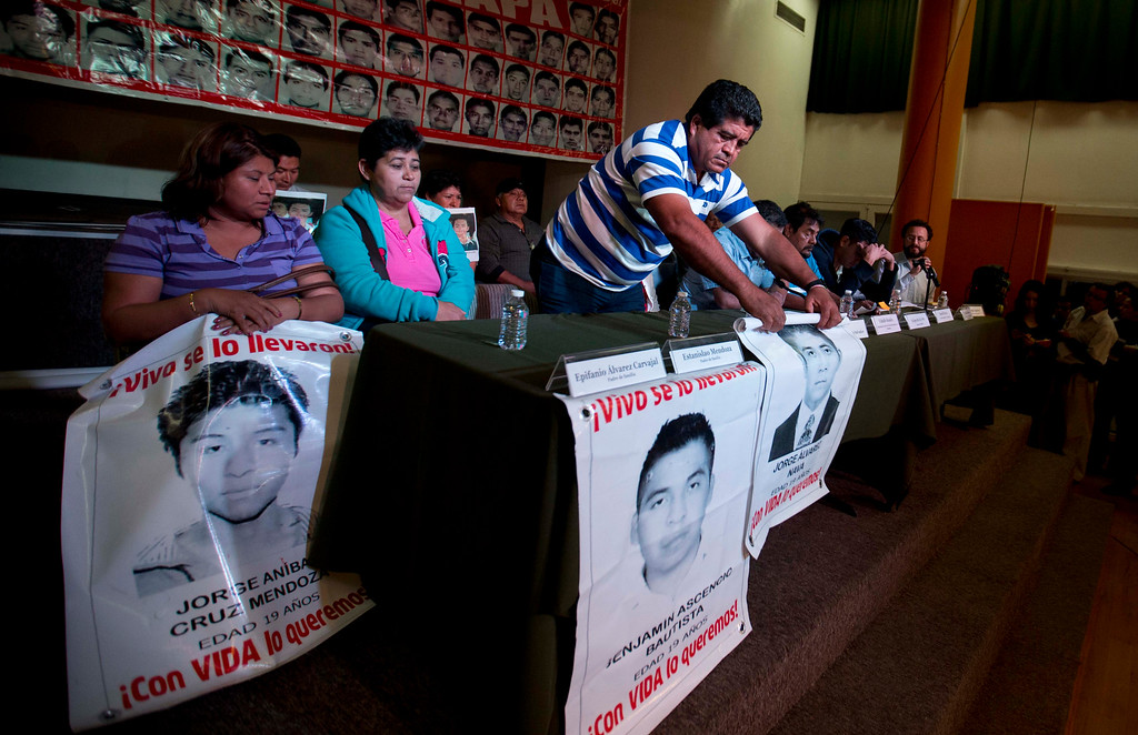 . Parents of missing students, some holding pictures of the missing, attend the press conference in Mexico, City, Tuesday Jan. 27, 2015. Mexican attorney general Jesus Murillo Karam said that investigators are now certain that 43 college students missing since September were killed and incinerated after they were seized by police in southern Guerrero state. It was the first time Murillo Karam said definitely that all were dead, even though Mexican authorities have DNA identification for only one student and a declaration from a laboratory in Innsbruck, Austria, that it appears impossible to identify the others. (AP Photo/Eduardo Verdugo)