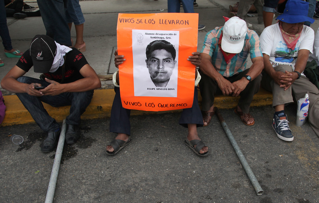 . The father of missing student Felipe Arnulfo Rosa holds his son\'s picture during a protest against the disappearance, and probable murder, of 43 students in the state of Guerrero, at the Acapulco airport in Mexico, Monday, Nov. 10, 2014. Supporters of the missing students, refusing to believe they are dead, have kept up the protests that have blocked major highways and set government buildings ablaze in recent weeks. The 43 teachers-school students disappeared at the hands of a city police force on Sept. 26 in the town of Iguala. (AP Photo/Marco Ugarte)