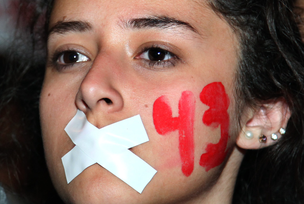. A demonstrators with her mouth taped shut and the number 43 painted on her face marches in protest for the disappearance of 43 students in the state of Guerrero, in Mexico City, Wednesday, Nov. 5, 2014. Federal police detained yesterday Iguala Mayor Jose Luis Abarca and his wife, Maria de los Angeles Pineda, who are accused of ordering the Sept. 26 attacks on teachers\' college students that left six dead and 43 still missing. (AP Photo/Marco Ugarte)