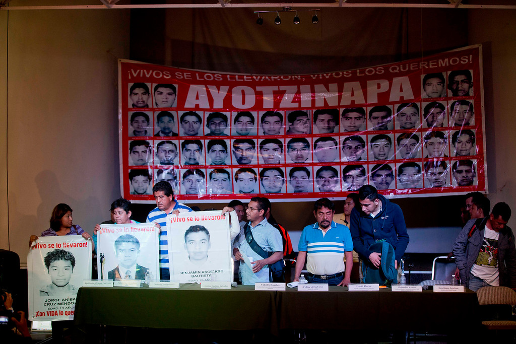 """. Parents of missing students, some holding pictures of the missing, stand in front of a banner with the photos of all of the disappeared students that reads in Spanish \""""They took them alive, We want them back alive,\"""" during a press conference in Mexico, City, Tuesday Jan. 27, 2015. Mexican attorney general Jesus Murillo Karam said that investigators are now certain that 43 college students missing since September were killed and incinerated after they were seized by police in southern Guerrero state. It was the first time Murillo Karam said definitely that all were dead, even though Mexican authorities have DNA identification for only one student and a declaration from a laboratory in Innsbruck, Austria, that it appears impossible to identify the others. (AP Photo/Eduardo Verdugo)"""