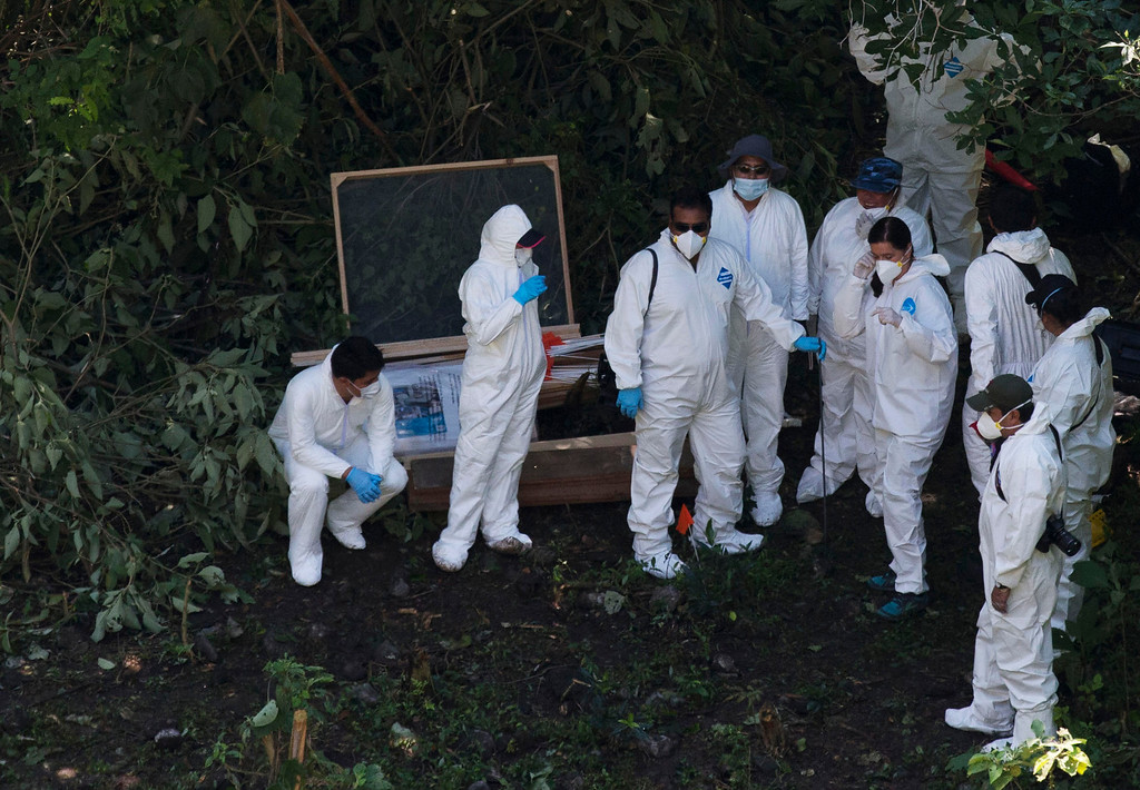 . Forensic examiners coordinate as they search for human remains below a garbage-strewn hillside in the densely forested mountains outside Cocula, in Guerrero state, Mexico, Tuesday, Oct. 28, 2014. Suspects arrested this week told prosecutors that many of the 43 students who disappeared Sept. 26 from the town of Iguala had been held near this location. (AP Photo/Rebecca Blackwell, Pool)