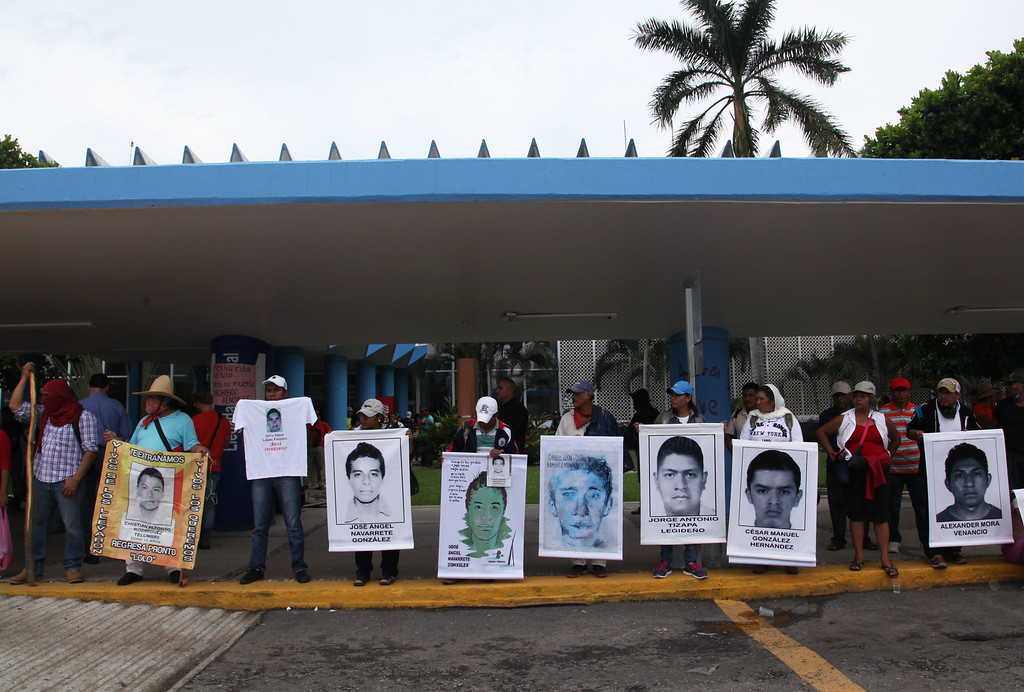 . The relatives of 43 missing students hold posters of their missing loved ones as they protest their disappearance, and probable murder, in the state of Guerrero, at the Acapulco airport in Mexico, Monday, Nov. 10, 2014. Supporters of the missing students, refusing to believe they are dead, have kept up the protests that have blocked major highways and set government buildings ablaze in recent weeks. The 43 teachers-school students disappeared at the hands of a city police force on Sept. 26 in the town of Iguala. (AP Photo/Marco Ugarte)