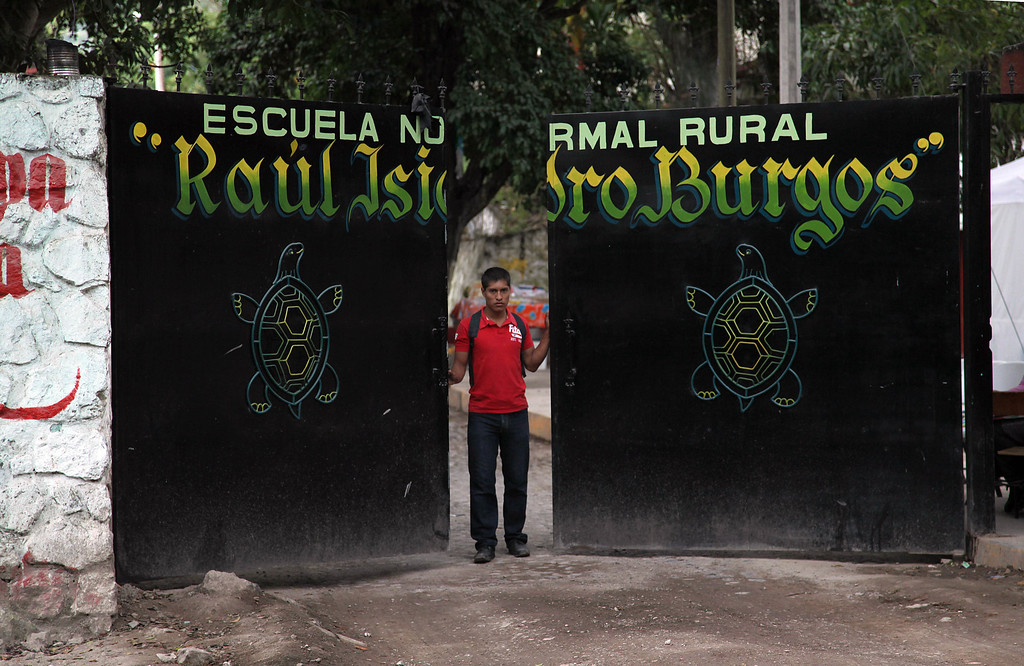 . In this Nov. 10, 2014 photo, a student closes the entrance gate to the Rural Normal School of Ayotzinapa, in Tixtla, Mexico. (AP Photo/Marco Ugarte)